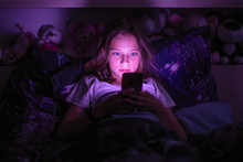 Little Girl Lying Under A Blanket Looking At The Smartphone At Night.