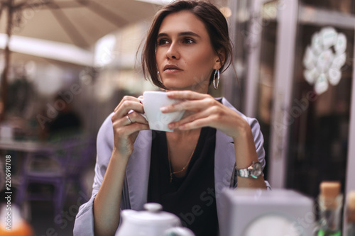 Fotografia  Attractive brunette bussines woman with tail drinking coffee or tea in restaurant