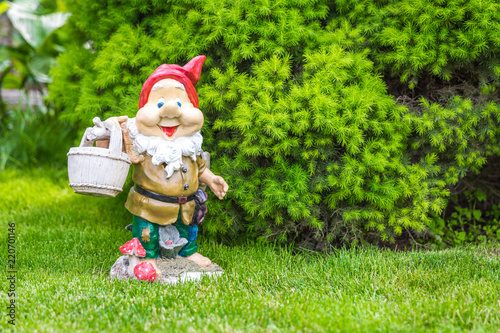 Photo garden dwarf in home garden, gnome decoration
