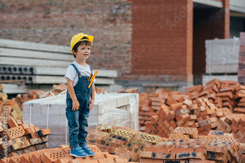 Fototapety, obrazy: Architect in helmet writing something near new building. little cute boy on the building as an architect.