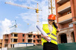 Woman engineer in helmet with rolls on construction site