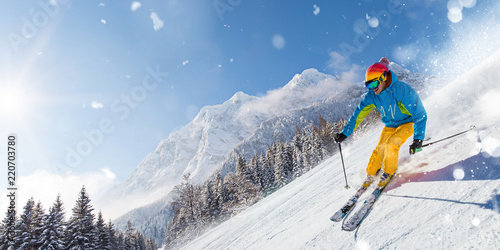 fototapeta na lodówkę Skier skiing downhill in high mountains