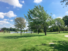 Green And Clean Lakeside Park With Pathway Trail System In Coppell, Texas, USA. Grassy Lawn Park With Mature Trees Under Sunny Summer Cloud Blue Sky