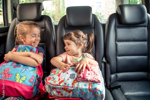 Children in the car go to school, happy, sweet faces of sisters Wallpaper Mural