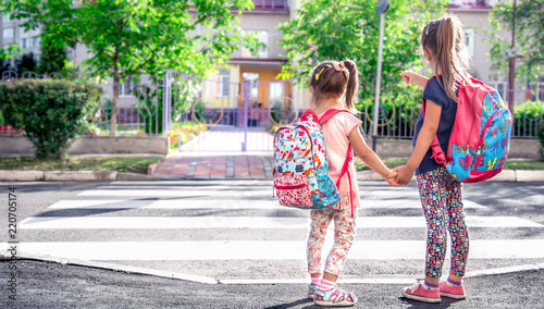 Fotografia, Obraz Children go to school, happy students with school backpacks and holding hands to