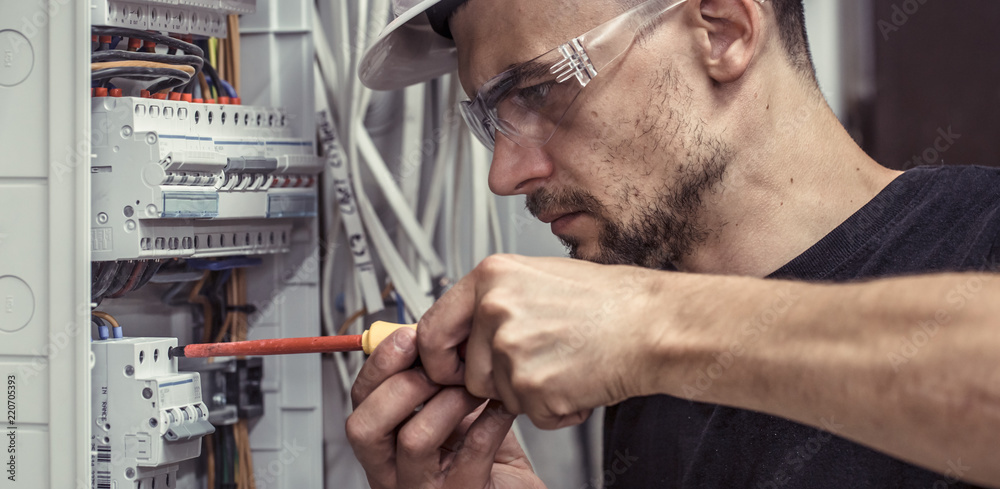 Fototapety, obrazy: a male electrician works in a switchboard with an electrical connecting cable