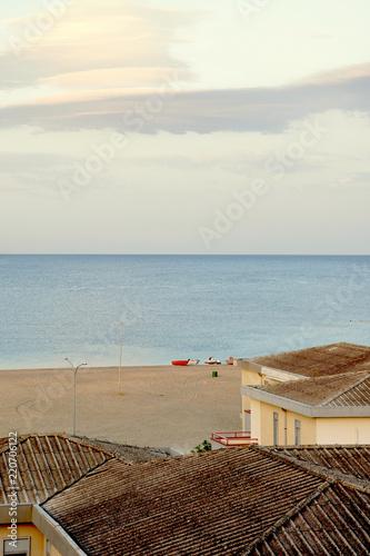 Photo Sandy beach Ionian Sea, southern Italy city Bova Marina, on the shore of the red fishing boat