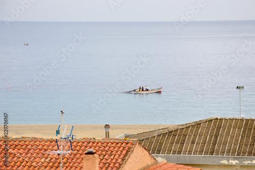 Obraz na plátně  Sandy beach of the Ionian Sea, South Italy city of Bova Marina, fishermen on a boat fishing