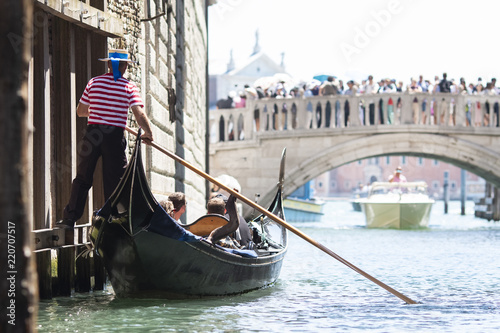 Foto op Plexiglas Venetie Venice, Italy - May 21, 2017: The gondola floats along the old narrow street in Venice. Gondola is the most attractive tourist transport in Venice.