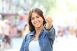 Leinwanddruck Bild Happy girl posing with thumb up in the street