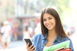 Leinwanddruck Bild Happy student posing holding a smart phone