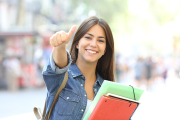 Obraz na Szkle Happy student posing with thumbs up in the street