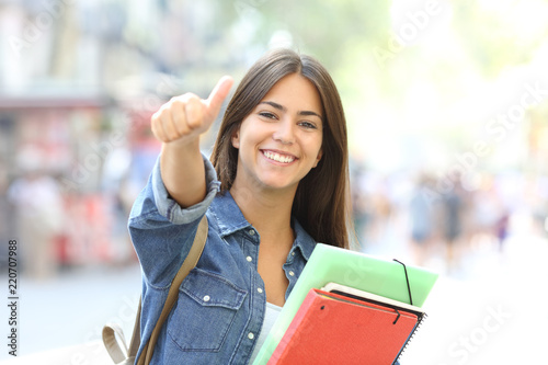 Happy student posing with thumbs up in the street Canvas Print