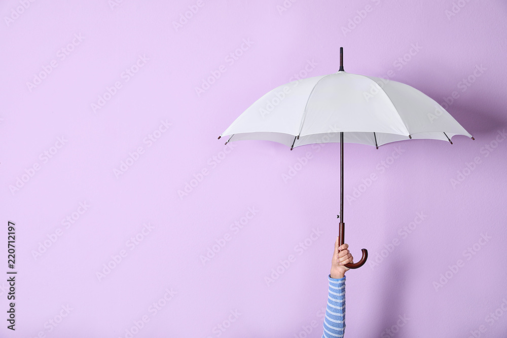 Fototapeta Person holding bright open umbrella on color background with space for design