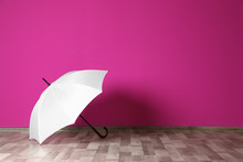 Beautiful Open Umbrella On Floor Near Color Wall With Space For Design