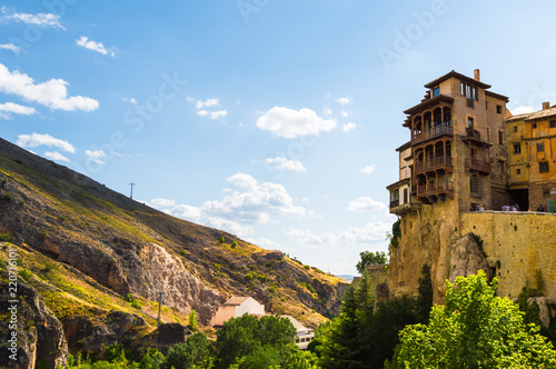 Sunny scene of the Hanged Houses (Casas Colgadas) and the mountains in the city of Cuenca, Spain. Touristic houses built on the rocks of a cliff.