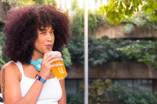 Fotografia, Obraz woman drinking orange juice with headphones