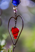 Red Wire Art Heart Against Green Pastel Bokeh Background