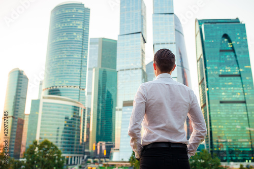 Fotografía  Back view of businessman looking on copy space while standing against glass skys