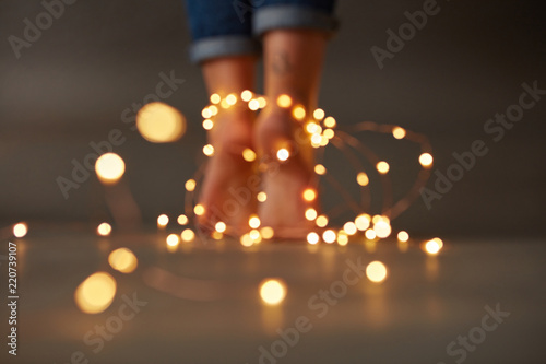 Valokuva  Christmas composition of female feet with garlands on the floor around a dark ba