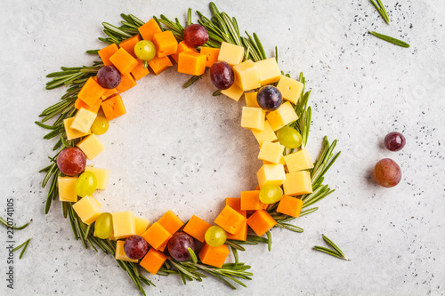 Christmas wreath of snacks from cheese and grapes, top view. Christmas food background concept.