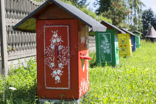 Fotografering  Painted old wooden beehives decorated with a hand painted colorful floral motive