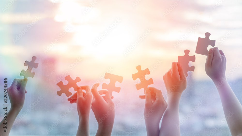Fototapeta Hands of children students holding pieaces of jiwsaw together as a symbol for autism or teamwork in school.