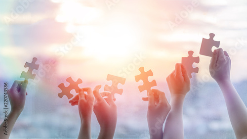 Fotografía  Hands of children students holding pieaces of jiwsaw together as a symbol for autism or teamwork in school
