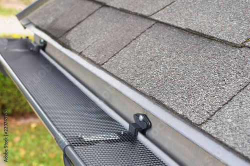 Fotografiet Plastic guard over new dark grey plastic rain gutter on asphalt shingles roof at shallow depth of field