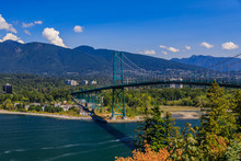 Lions Gate Or First Narrows Bridge In Stanley Park Vancouver Canada With North Vancouver And Mountains In The Background