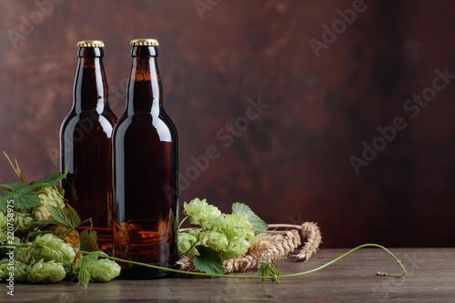 Tuinposter Bier / Cider Bottles of beer, grain and hops on a old wooden table.