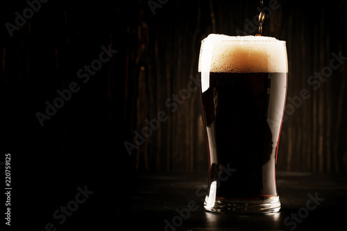 Photo sur Aluminium Biere, Cidre Dark english beer, ale or stout is poured into glass, dark bar counter, space for text, selective focus