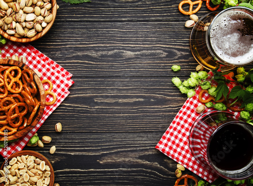 In de dag Bier / Cider Light and dark german beer in big mugs and bowls with salty snacks and nuts, autumn beer festival concept, dark wooden table, top view