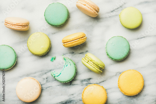 Flat-lay of sweet colorful French macaroon cookies over grey marble background, top view, horizontal composition