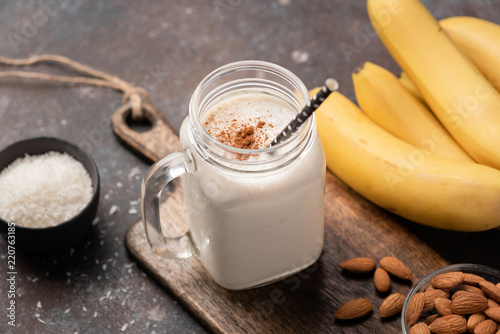 Keuken foto achterwand Milkshake Banana protein smoothie or milkshake with cinnamon and coconut in a drinking jar with staw. Closeup view, selective focus