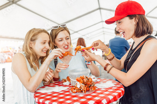 Foto  Group of young multiracial girl friends eating seafood crab or crawfish at a out