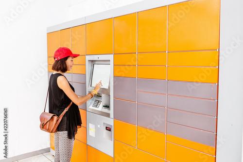 Fotografia, Obraz Woman client using automated self service post terminal machine or locker to rec
