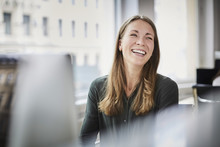 Smiling Businesswoman Looking Away While Sitting By Window At Office