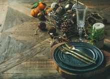 Christmas Or New Year Eve Holiday Table Setting. Plates, Silverware, Glass, Pine Cone, Candle And Toy Festive Decorations Over Vintage Table Background, Copy Space, Selective Focus