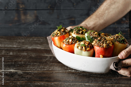 Fototapeta Male hands holding Healthy vegetarian food stuffed peppers copy space obraz