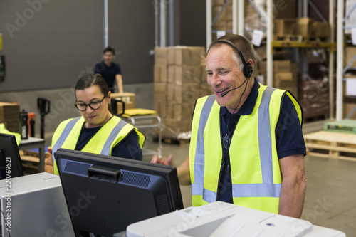 Confident senior male customer service representative talking through headset while standing by coworker in distribution