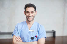 Portrait Of Smiling Young Male Nurse In Blue Scrubs Standing With Arms Crossed Against Wall At Hospital