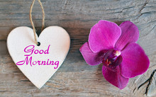 Good Morning.Decorative White Wooden Heart With Text And Pink Orchid Flower On Old Wooden Background.Selective Focus.