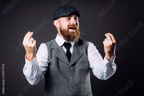 Fototapeta A bearded man in suit talking and gesticulating like italian on black background obraz