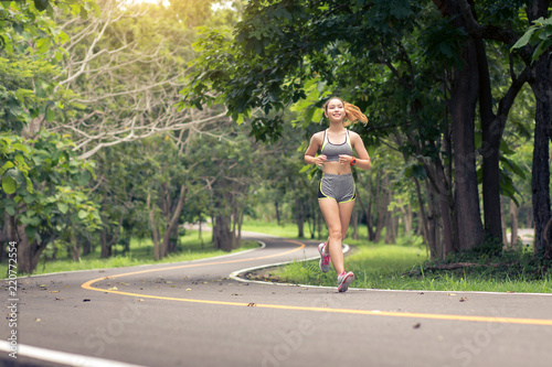 Woman exercising and jogging outdoors in nature at the park
