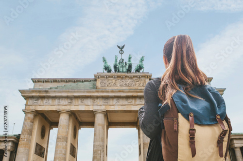 Fotografia A tourist girl with a backpack or student looking at the Brandenburg Gate in Berlin in Germany