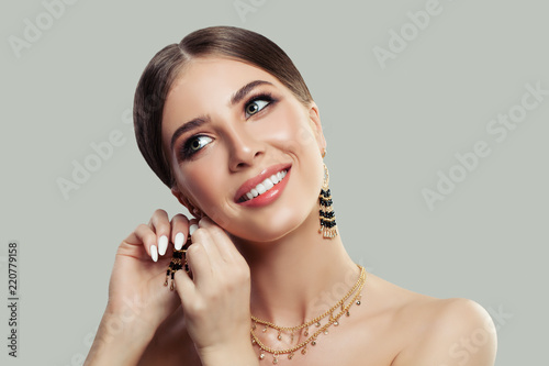 Fotografie, Tablou Beautiful smiling woman puting on gold fashion jewelry earrings with black gemstones