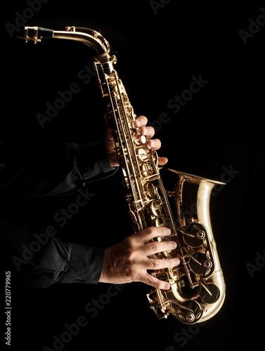 Vászonkép Musician playing alt saxophone on black