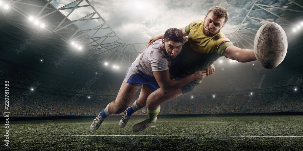 Fototapety, obrazy: Two male Rugby players fight for the ball in flight on professional rugby stadium