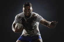 Isolated Dirty Rugby Player With Rugby Ball On Dark Background